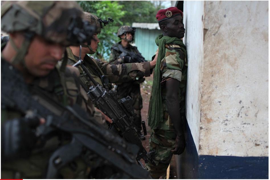 Des soldats français contrôlent un soldat de la Séléka dans les rues de Bangui.